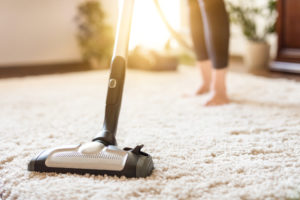 woman vacuuming after choosing a vaccum cleaner for her household situation